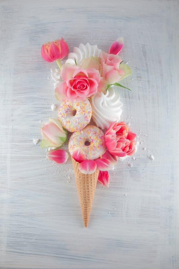 Конус мороженого waffle Flatlay сладостный с розовыми тюльпанами и цветением роз цветет над белой деревянной предпосылкой, взгляд стоковые фотографии rf