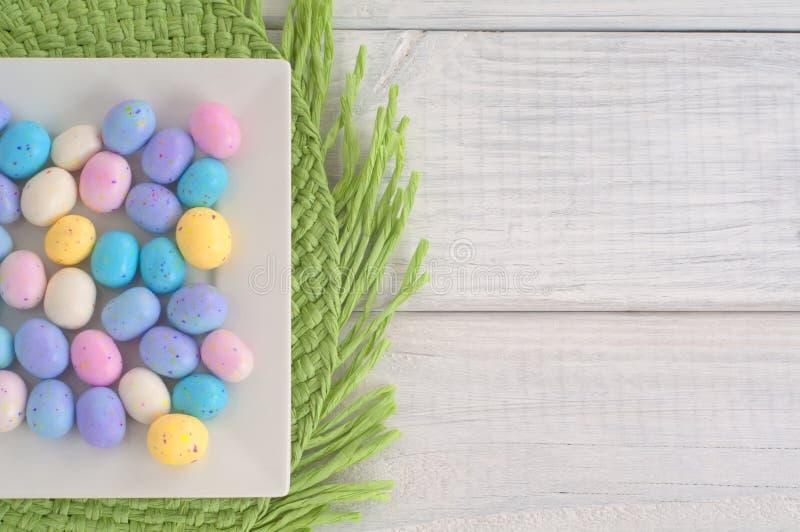 Конфета пасхального яйца на квадратной тарелке на зеленом Placemat на белых деревянных досках как предпосылка стоковое изображение
