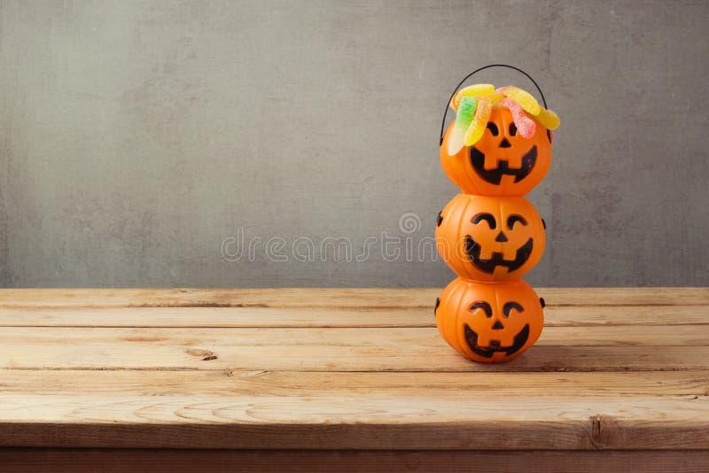 Конфета фокуса или обслуживания праздника хеллоуина с ведром фонарика jack o на деревянном столе стоковые изображения rf