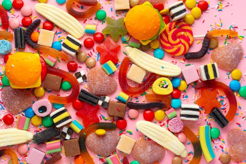 Конфеты со студнем и брызгают красочный массив различных помадок и обслуживаний childs над пинком как праздничная предпосылка стоковые фото
