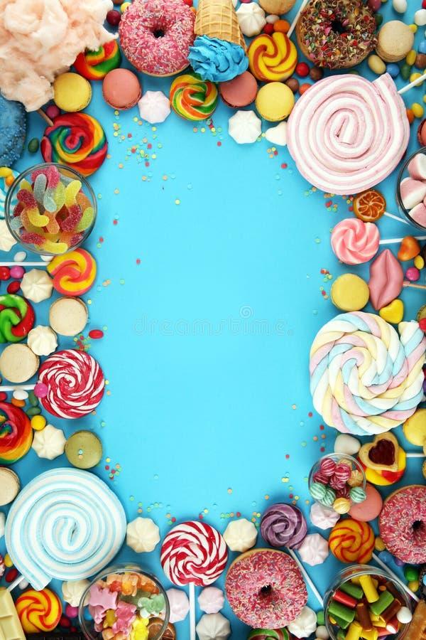 Конфеты с студнем и сахаром красочный массив различных помадок и обслуживаний childs на сини стоковое изображение