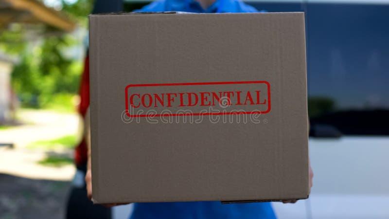 Конфиденциальный курьер пакета в равномерной держа картонной коробке, доставке документа стоковое изображение rf