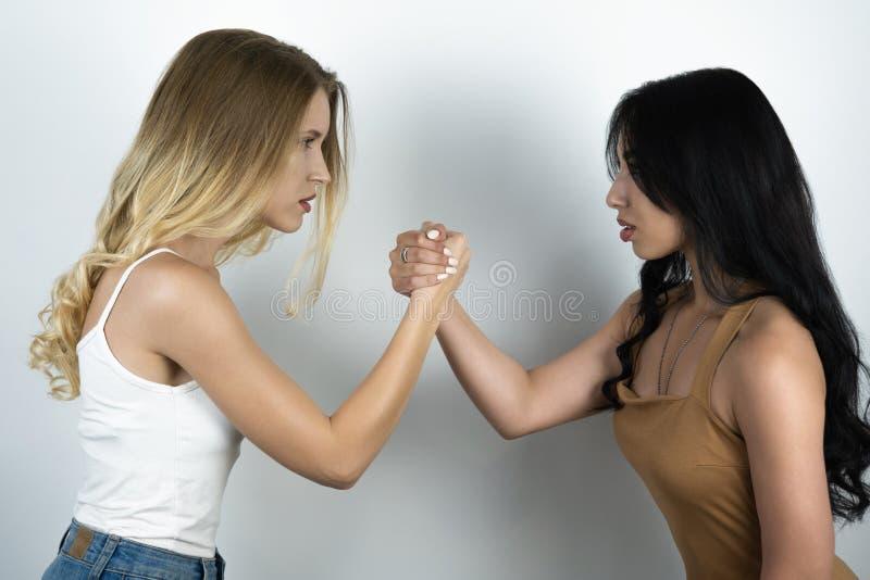 Конфронтация между блондинкой и предпосылкой брюнета белой стоковые изображения rf