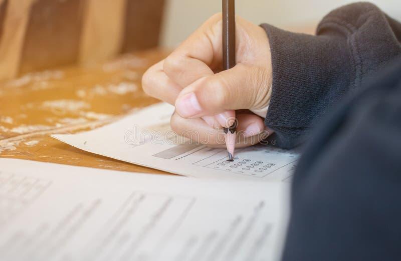 Концентрация студентов держа карандаши в руке делая викторины разнообразного выбора испытывая тренировки листов ответа экзаменов  стоковые фото