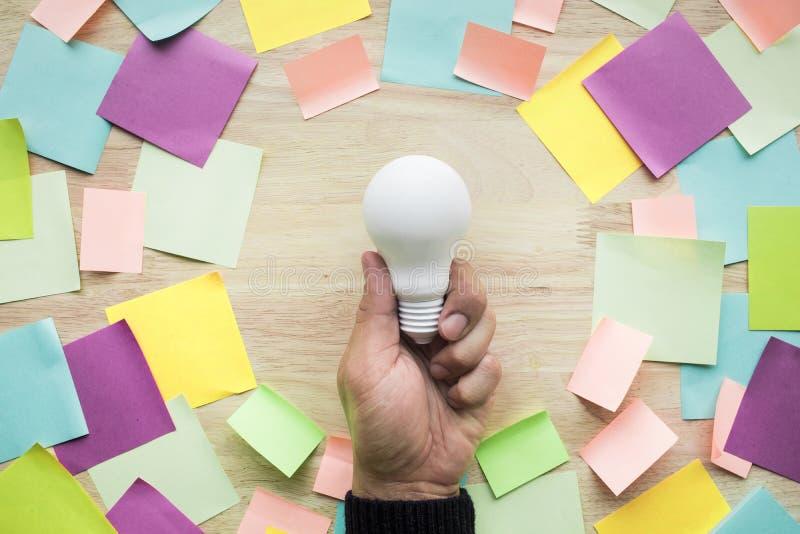 Концепции идей воодушевленности при рука держа белую лампочку стоковые изображения rf
