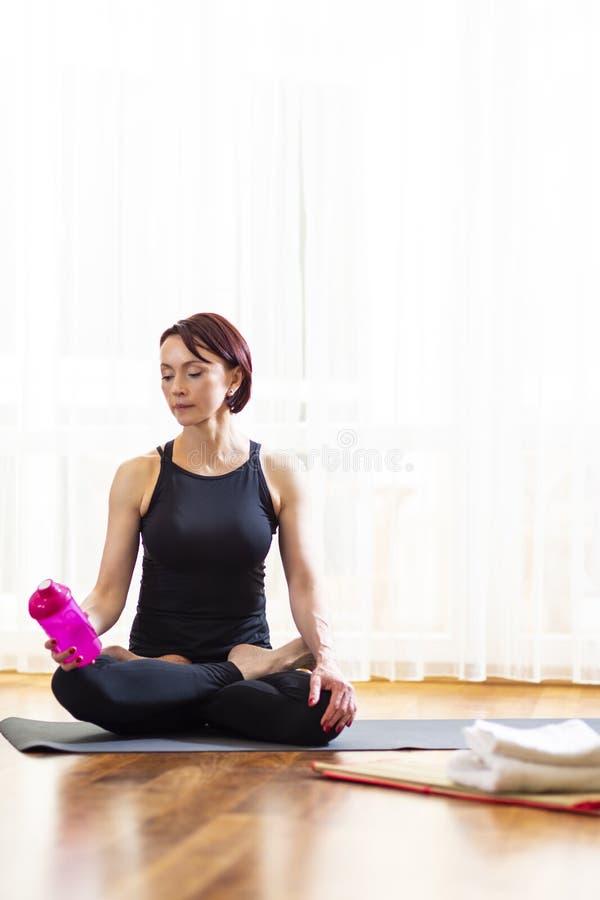 Концепции образа жизни йоги Спокойная кавказская женщина в представлении йоги внутри помещения Представлять перед большим окном с стоковое фото