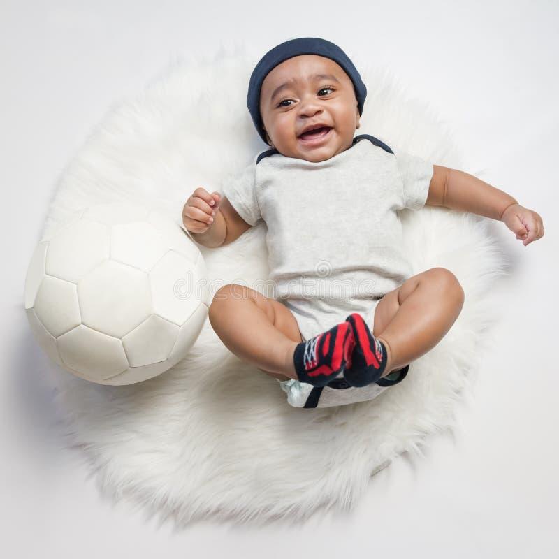Концепции футбола футбола photoshoot потехи ребёнка улыбка младенческой большая имея потеху играя смеясь над класть на белый мехо стоковая фотография