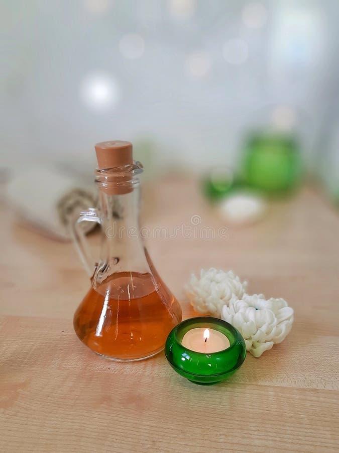 Концепция ароматерапии спа Полотенце, эфирное масло, handmade мыло цветка, горя свеча в зеленом стекле на деревянном столе стоковые фотографии rf