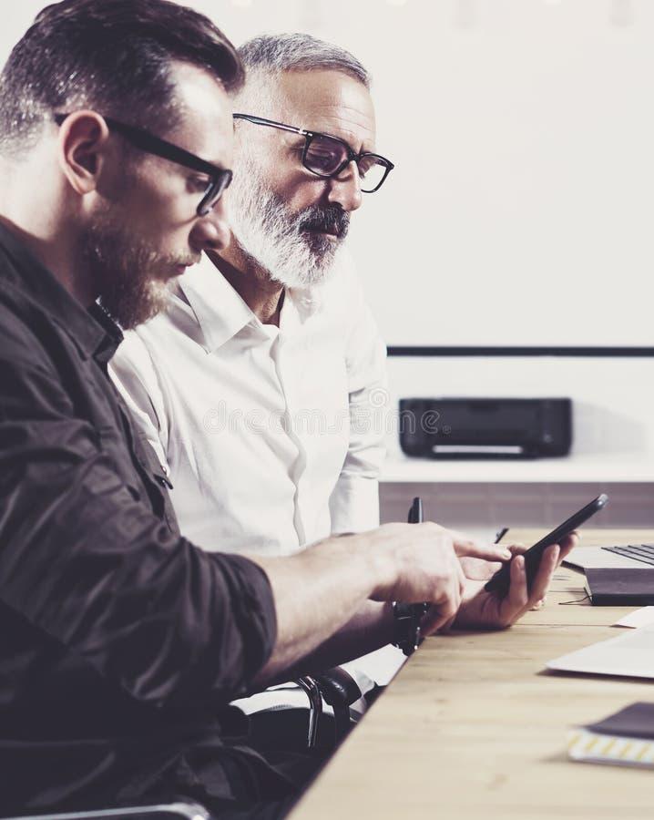 Концепция бизнесменов встречая процесс Бородатый молодой человек держа мобильный телефон и касающий экран Взрослый бизнесмен стоковые фото