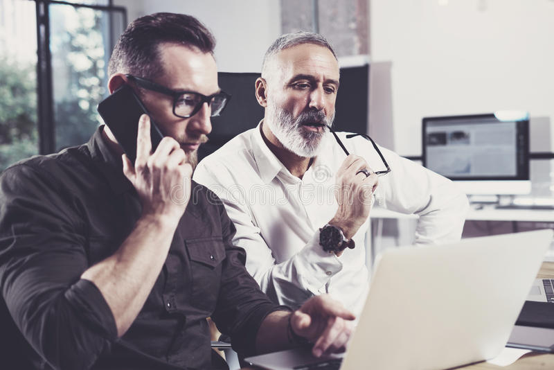 Концепция бизнесменов коллективно обсуждать процесс Бородатый молодой человек используя коллеги мобильного телефона и взрослого с стоковые фото