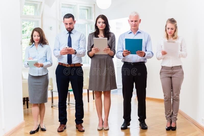 Концепция - бизнесмены в офисе стоя в строке стоковая фотография
