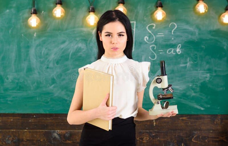Концепция биологии Дама в официально носке на спокойной стороне в классе Ученый дамы держит книгу и микроскоп, доску дальше стоковое изображение