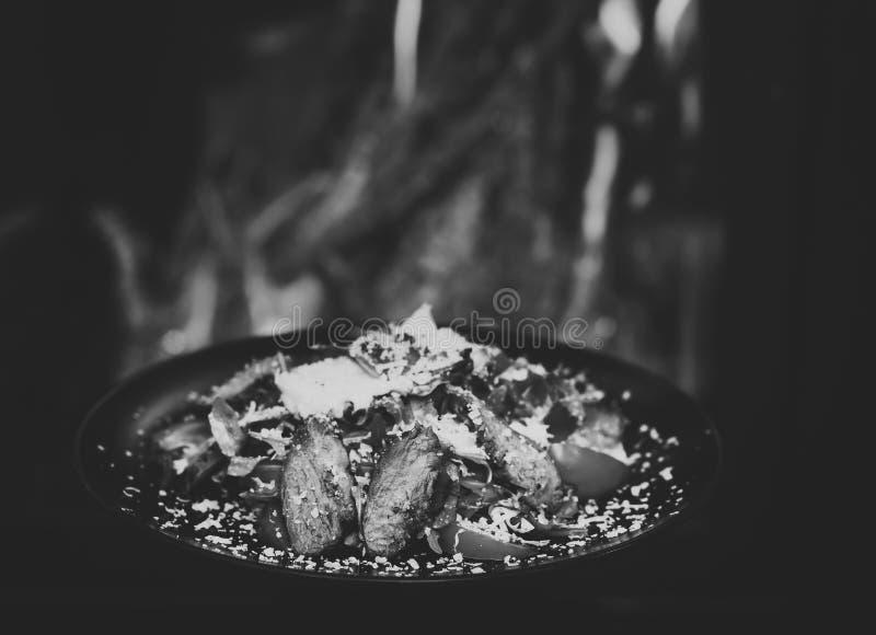 Концепция блюда ресторана Блюдо говядины или телятины, который служат с листьями салата, томатами и брызгаемые с сыр пармесаном стоковые изображения rf