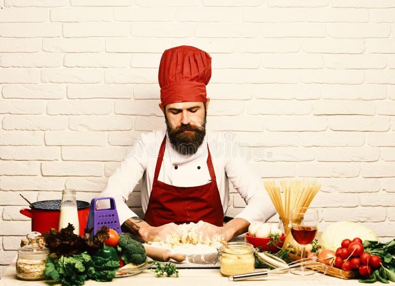 Концепция варочного процесса Шеф-повар делает тесто Кашевар с серьезной стороной в бургундской форме стоковая фотография rf