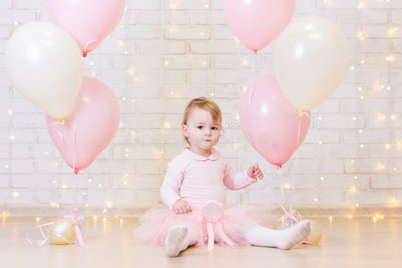 Концепция вечеринки по случаю дня рождения - маленькая девочка над предпосылкой кирпичной стены стоковые изображения