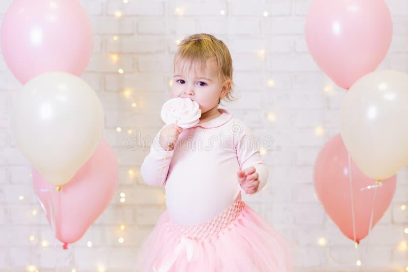 Концепция вечеринки по случаю дня рождения - портрет маленькой девочки есть помадки o стоковая фотография rf