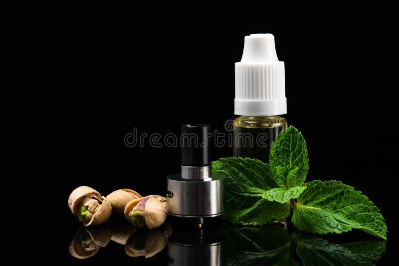 Концепция вкусов гайки и мяты для электронных сигарет на черной предпосылке стоковые изображения rf