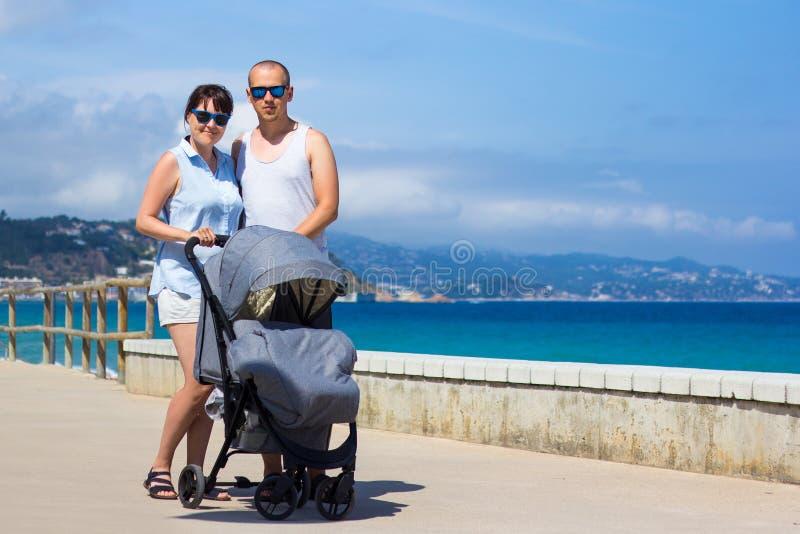 Концепция воспитания и перемещения - молодые родители с детской сидячей коляской стоковое изображение