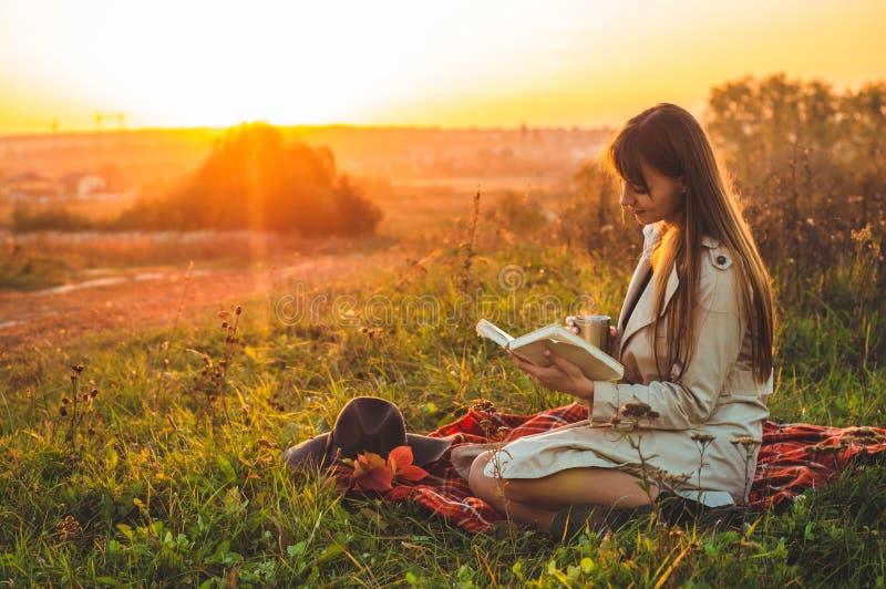 Концепция воссоздания образа жизни на открытом воздухе в осени Девушка со шляпой прочитала книги на шотландке с термо- чашкой Осе стоковые фотографии rf