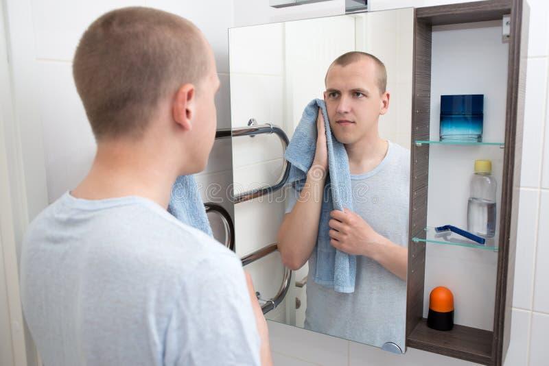 Концепция гигиены - красивый человек смотря зеркало после брить I стоковое изображение