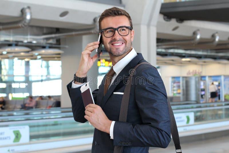 Концепция глобального бизнеса с бизнесменом на его сотовом телефоне изолированном на авиапорте стоковое изображение