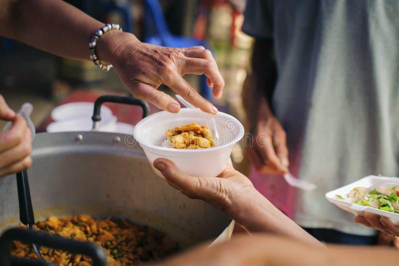 Концепция голода: Потребности еды бедных в помощи общества с пожертвованием еды: Бездомные комплектуют вверх еду призрения от стоковые фото