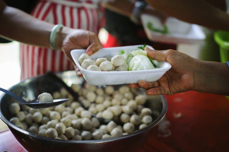Концепция голода: Потребности еды бедных в помощи общества с пожертвованием еды: Бездомные комплектуют вверх еду призрения от стоковые изображения