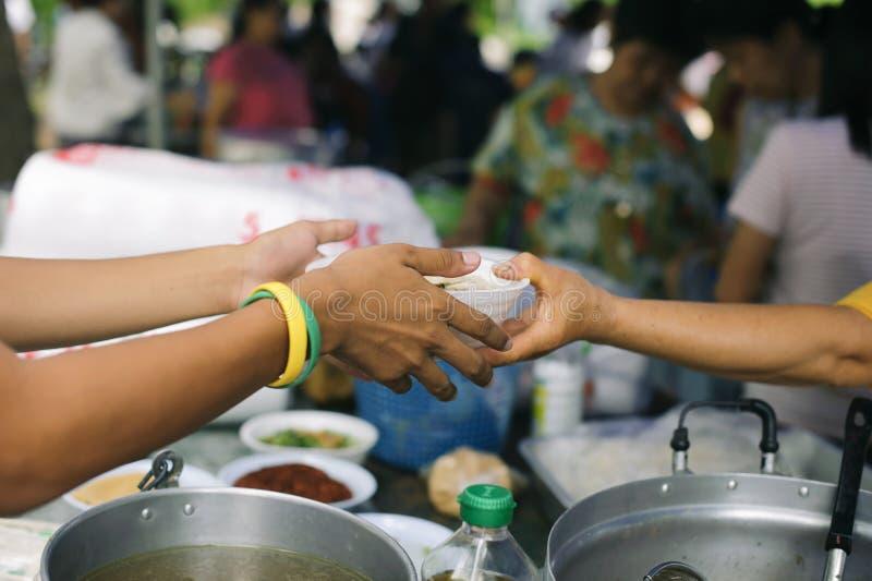 Концепция голода: Потребности еды бедных в помощи общества с пожертвованием еды: Бездомные комплектуют вверх еду призрения от стоковое фото rf
