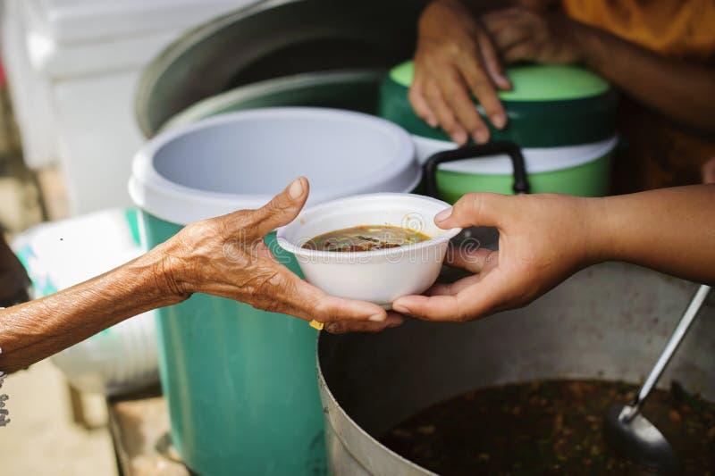 Концепция голода: Потребности еды бедных в помощи общества с пожертвованием еды: Бездомные комплектуют вверх еду призрения от стоковая фотография rf