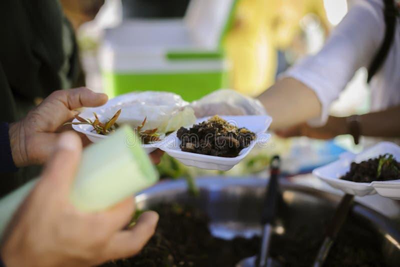 Концепция голода: Потребности еды бедных в помощи общества с пожертвованием еды: Бездомные комплектуют вверх еду призрения от стоковое фото
