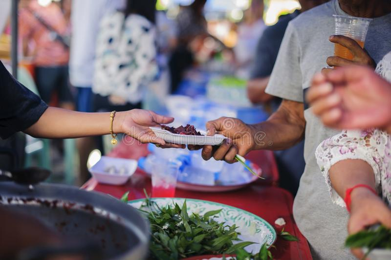 Концепция голода: Потребности еды бедных в помощи общества с пожертвованием еды: Бездомные комплектуют вверх еду призрения от стоковая фотография