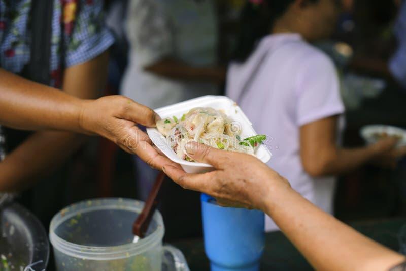 Концепция голода: Потребности еды бедных в помощи общества с пожертвованием еды: Бездомные комплектуют вверх еду призрения от стоковые изображения rf
