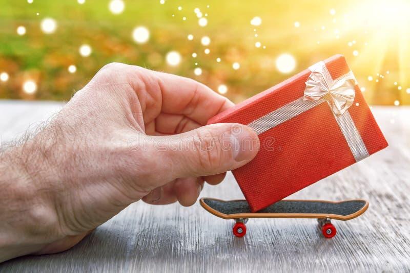 Концепция давать подарки рука катается на коньках малая подарочная коробка на мини скейтборде Дайте подарки и сделайте сюрприз Во стоковая фотография rf