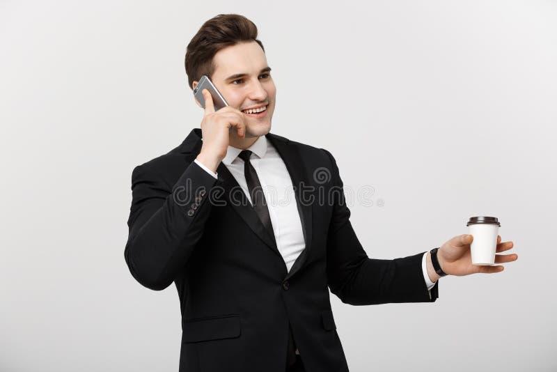 Концепция дела: Бизнесмен конца-вверх уверенно молодой красивый говоря на сотовом телефоне и выпивая кофе над белизной стоковые фото