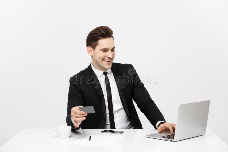 Концепция дела и образа жизни: Бизнесмен портрета усмехаясь сидя в офисе и ходить по магазинам онлайн оплачивает кредитной карточ стоковое изображение