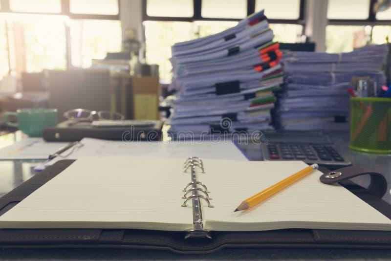 Концепция дела и финансов карандаша и тетради на столе офиса с стогом бумаги дела стоковые изображения rf