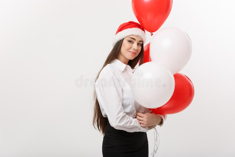 Концепция дела - красивая молодая уверенно бизнес-леди при шляпа santa держа воздушный шар празднует для рождества стоковое изображение rf