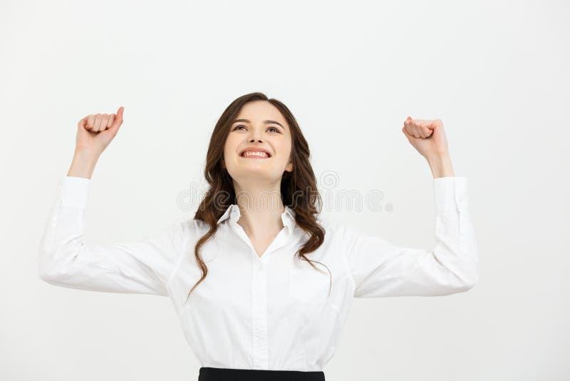 Концепция дела: молодая счастливая коммерсантка с руками в воздухе празднует успех на белой предпосылке стоковые изображения rf