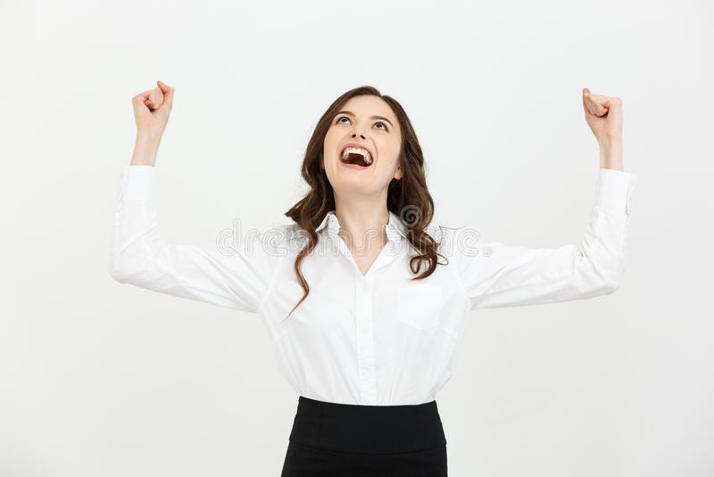 Концепция дела: молодая счастливая коммерсантка с руками в воздухе празднует успех на белой предпосылке стоковое изображение rf