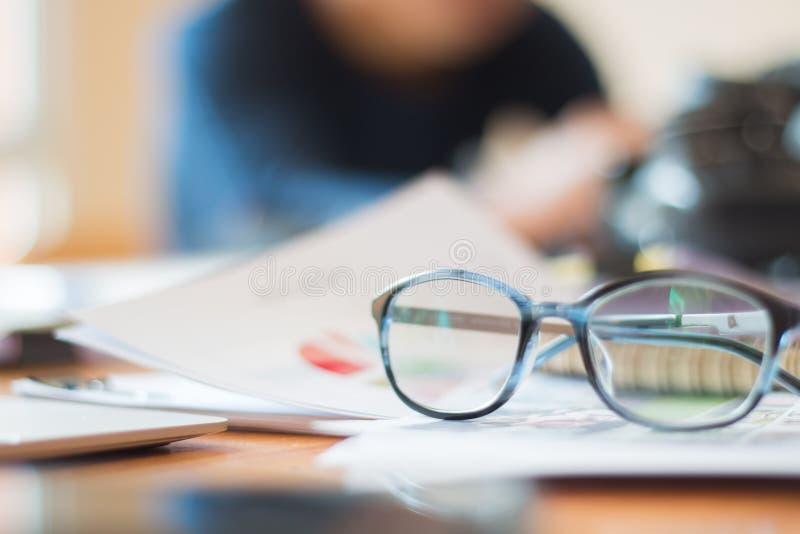 Концепция дела офиса документа занятая: Eyeglasses помещенные на документах тетради в грязном офисе с людьми нерезкости и занятым стоковое изображение rf