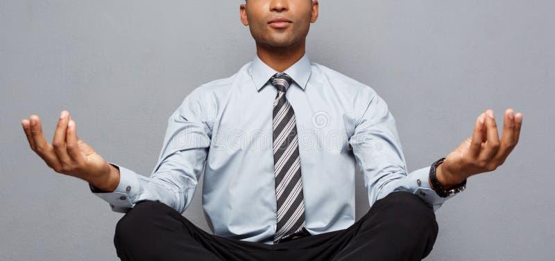 Концепция дела - портрет Афро-американского бизнесмена делая раздумье и йогу внутри перед работой стоковые изображения