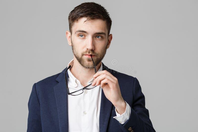 Концепция дела - портрет красивого бизнесмена в костюме с думать стекел серьезный с напряжённым выражением лица Isol стоковое фото rf