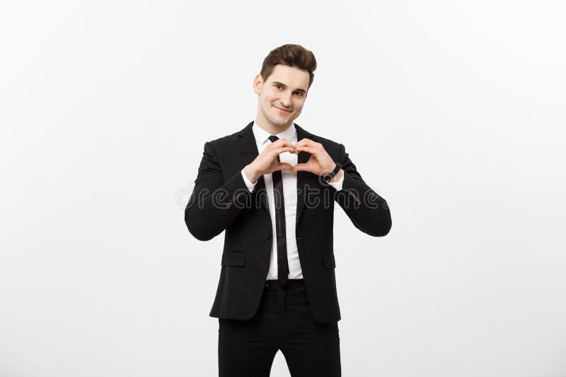 Концепция дела: Портрет очаровательного привлекательного бизнесмена держа руки в жесте сердца и поднимая брови пока стоковые изображения