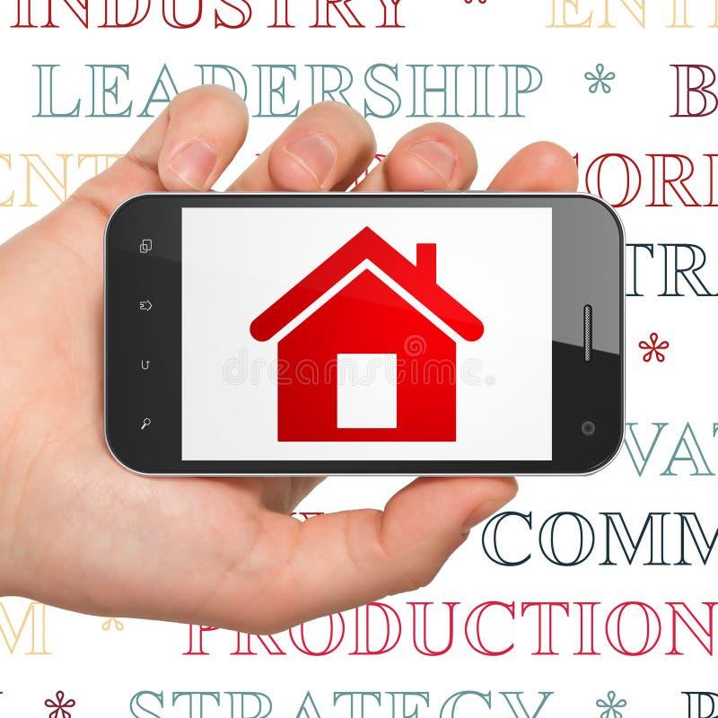 Концепция дела: Рука держа Smartphone с домом на дисплее стоковые изображения