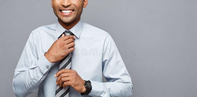 Концепция дела - счастливый уверенно профессиональный Афро-американский бизнесмен представляя над серой предпосылкой стоковое фото rf