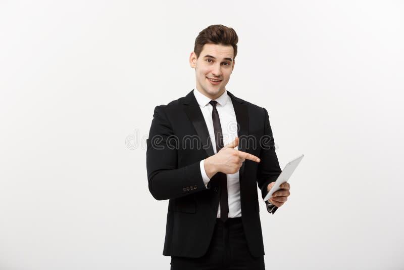 Концепция дела: Счастливый усмехаясь бизнесмен указывая на цифровую таблетку на белой предпосылке стоковое изображение