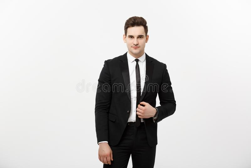 Концепция дела: Улыбка молодое красивое Гай красивого человека счастливая в умном костюме представляя над серой предпосылкой стоковая фотография