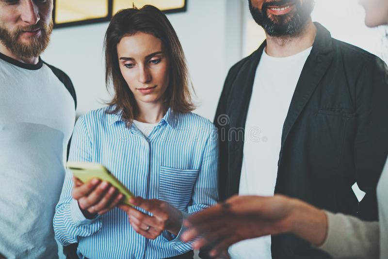 Концепция деловой встречи сотрудников Молодые женщины держа передвижные руку smartphone и новости обсуждения с ее коллегами стоковые фотографии rf