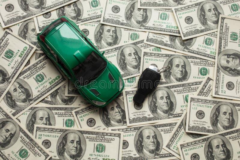 Концепция денег, кредит, новые автокредиты Много предпосылка 100 долларов, зеленый автомобиль и ключ стоковое фото