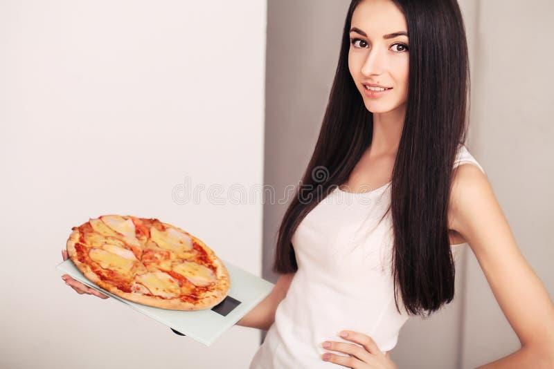 Концепция диеты и фаст-фуда Полная женщина стоя на веся масштабе держа пиццу Нездоровая высококалорийная вредная пища Dieting, об стоковые изображения rf